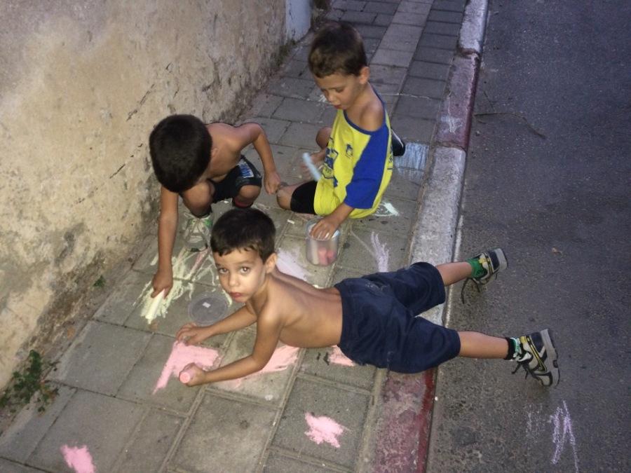 מתן, מיכאל ודניאל מציירים בגיר על המדרכה.